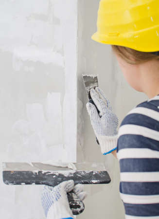 putty knives: Female plasterer repairs wall with spackling paste