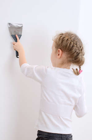 Little girl repairs wall with spackling paste  photo