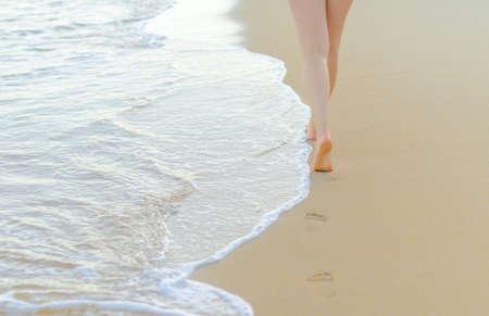 Pair of female legs on a seashore  photo