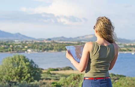 mujer mirando el horizonte: Mujer bonita con el mapa de vacaciones.