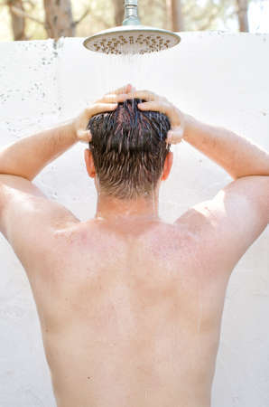 Man having shower outdoors  View from the back  photo