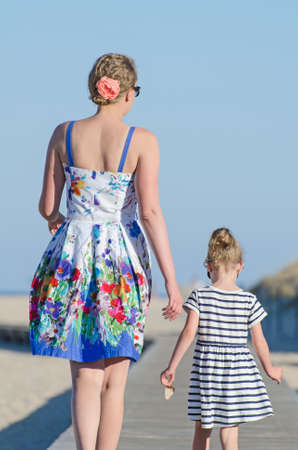 Little girl with mom on beach vacation. photo