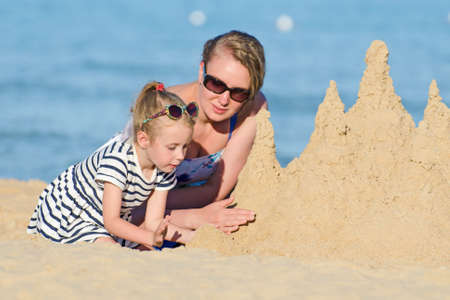 Family with sand castle on the beach. photo