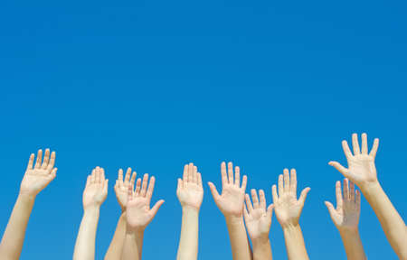 hand lifted: Many hands raised up against the blue sky  Stock Photo