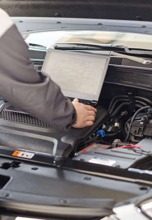 Mechanic with laptop diagnoses car in workshop  photo