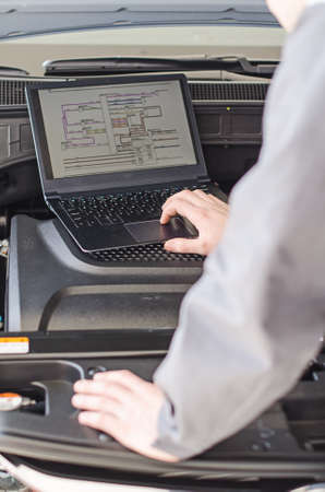 Mechanic with laptop diagnoses car in workshop