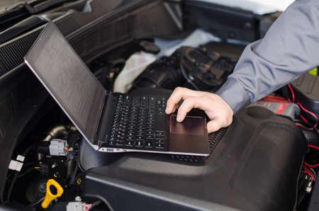ワーク ショップで車を診断するメカニック ノート パソコン 写真素材