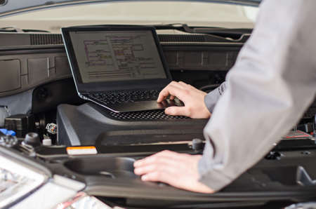 diagnoses: Mechanic with laptop diagnoses car in workshop