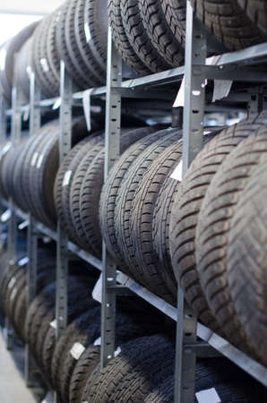 Used old car tires at warehouse Reklamní fotografie - 27861791