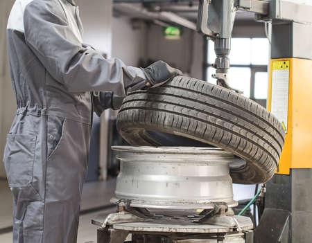 auto mechanic: Mechanic changing car tire with bead breaker tool