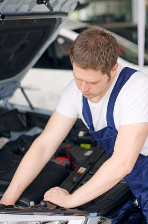 Young mechanic repairing car in service center photo