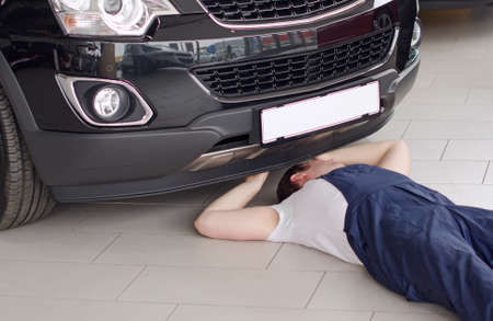 Young mechanic under car in service center  photo