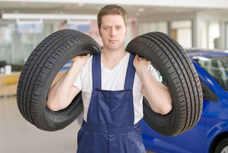 Young mechanic with tires in service center  photo