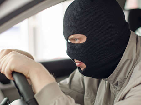 looting: Thief in mask steals expensive new car  Stock Photo