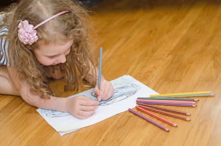 prodigy: Little girl drawing car with colored pencils  Stock Photo