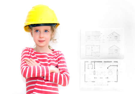 Little girl in hard hat standing near the wall with house plan  photo