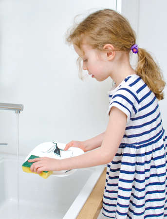 Little girl washing the dishes in the kitchen. photo
