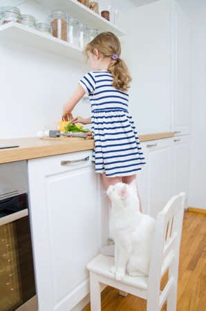 Little girl making meal in the kitchen. Imagens