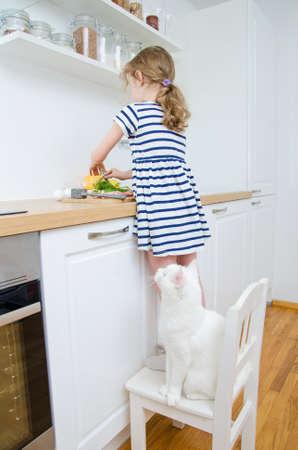 Niña que hace la comida en la cocina. Foto de archivo