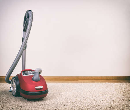 Red vacuum cleaner in empty room. Photo with vignette. Stock Photo