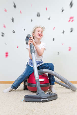 home appliances: Cute little girl singing during cleaning the flat.