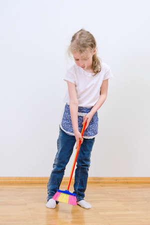 brooming: Little cute girl brooming floor at home.