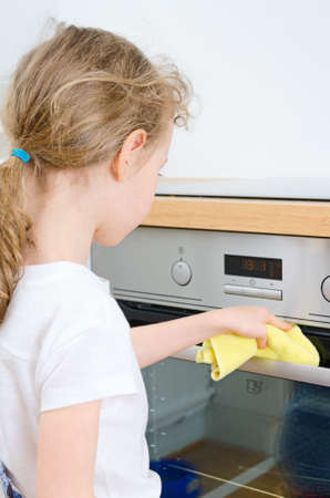 Little girl wipes oven in the kitchen at home  photo