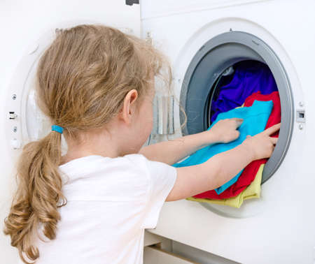 Little girl doing laundry  Housework concept  photo