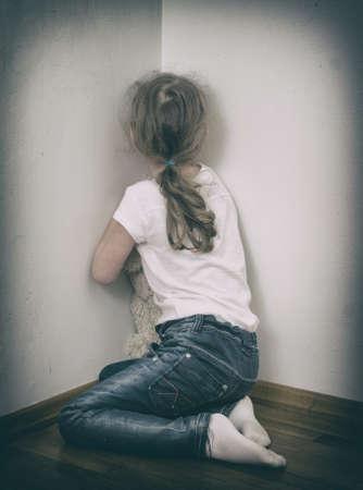 コーナーの家庭内暴力概念で泣いている少女