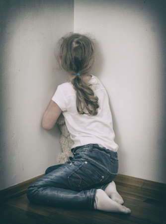 Little girl crying in the corner  Domestic violence concept  Stock Photo