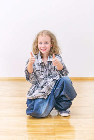 Smiling little girl in oversized jeans and shirt. photo