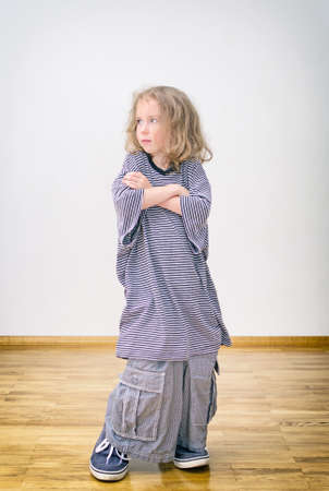 Little girl posing in oversized shorts and shirt. photo