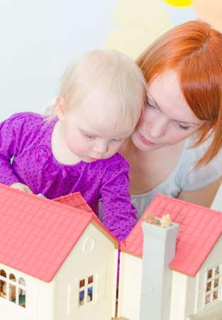 puppenhaus: Kleines M�dchen und Mutter, die mit Puppenhaus.