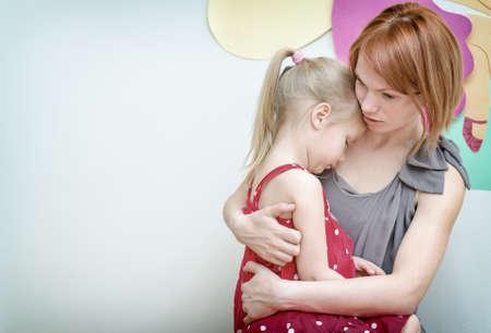 Mutter, die ihr trauriges Kind umarmt.