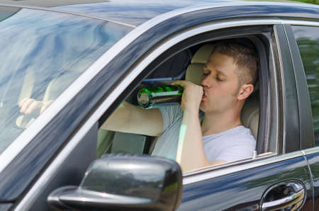 drinking alcohol: Driving Under the Influence  Man drinking alcohol in the car  Stock Photo