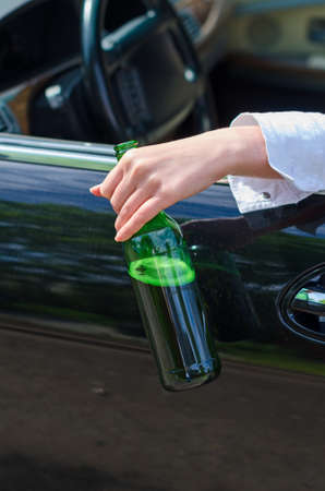 Driving Under the Influence  Female hand with bottle of beer  photo