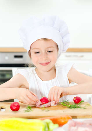 Little girl in chef hat cooking in kitchen. photo