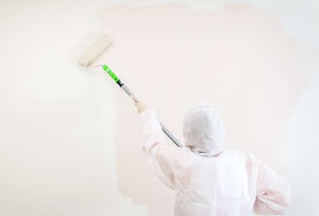 protective suit: Painter in protective suit paints the wall  Stock Photo