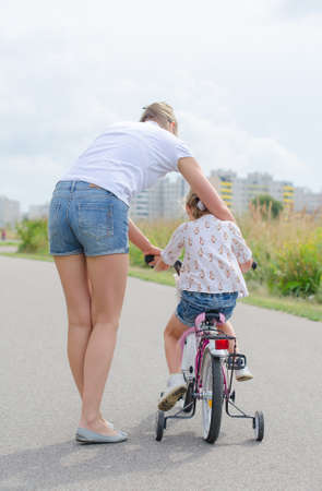 Woman teaching little girl to ride a bicycle  Stock Photo - 30611772