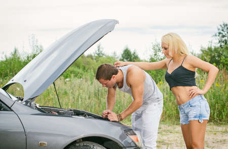 Man and woman near the broken car. photo
