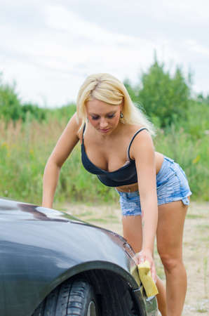 Sexy woman washing car with sponge  photo