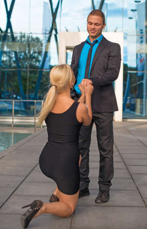marriage proposal: Woman standing on one knee and making proposal to man