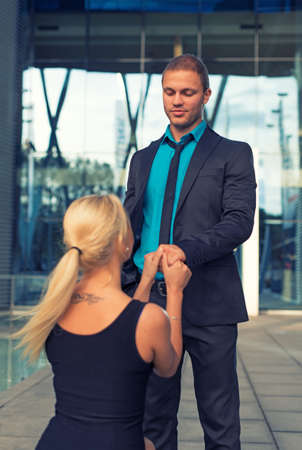 faithlessness: Woman standing on one knee and making proposal to man. Stock Photo