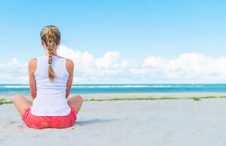 Pigtailed girl sitting on the beach and meditating. photo