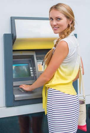 ATM からお金を引き出すのきれいな女性