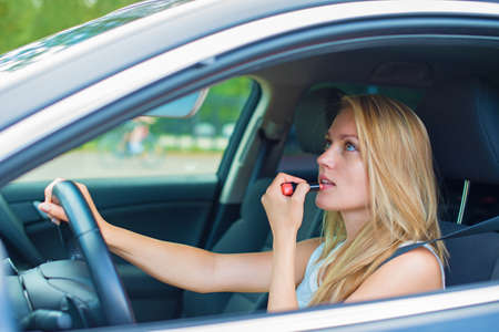 Beautiful young woman applying make-up while driving car  photo