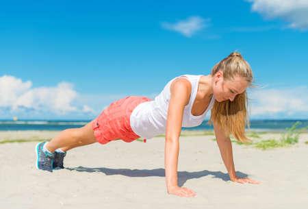 pushups: Woman doing push-ups on the beach.