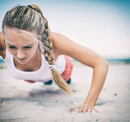 hard: Woman doing push-ups on the beach. Vintage effect.