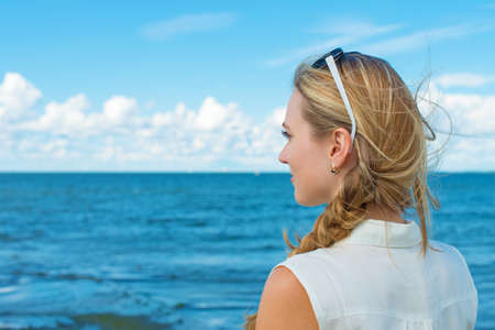 Woman standing near the sea and waiting for the ship. photo