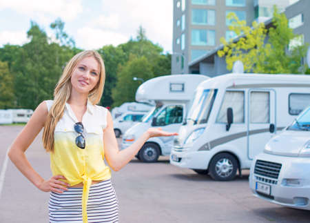 Beautiful young woman offers campervans at shop